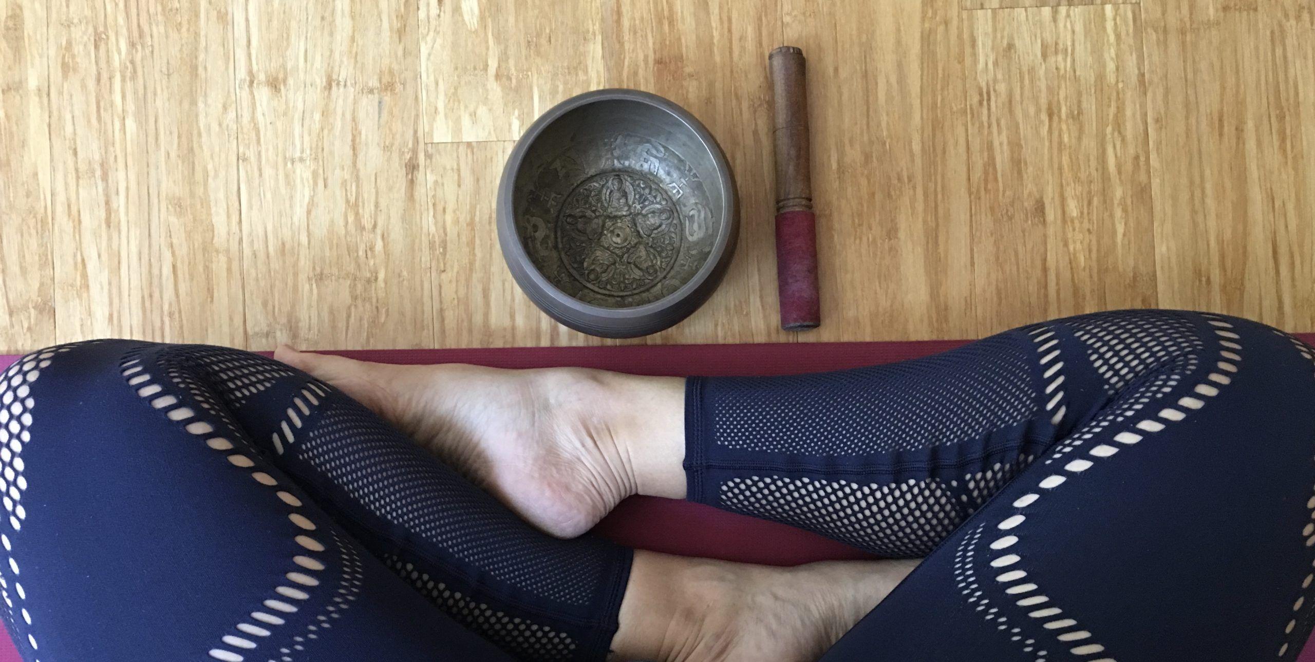Yoga leggings and singing bowl in cross legged seat